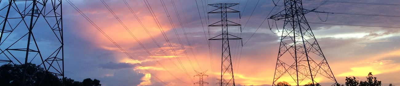 Electricity pylons against evening sky